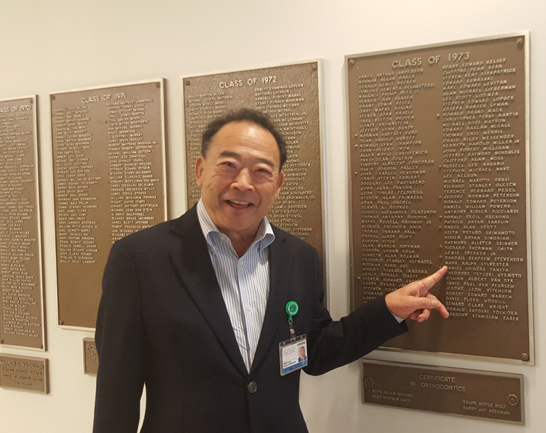 Dr. Dan Tanita in front of the donor wall