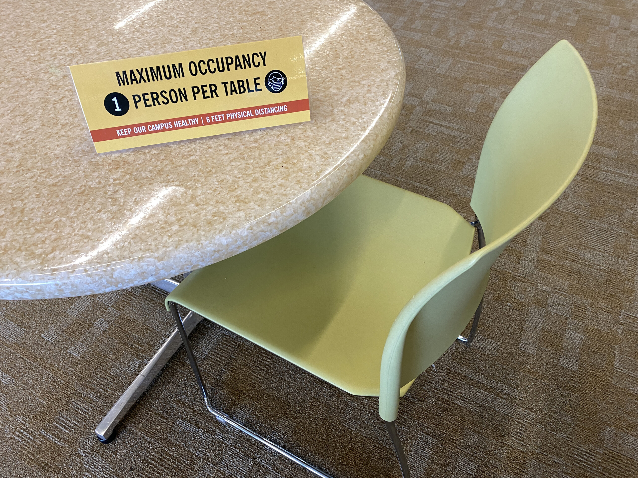 table with sign saying only one occupant per table